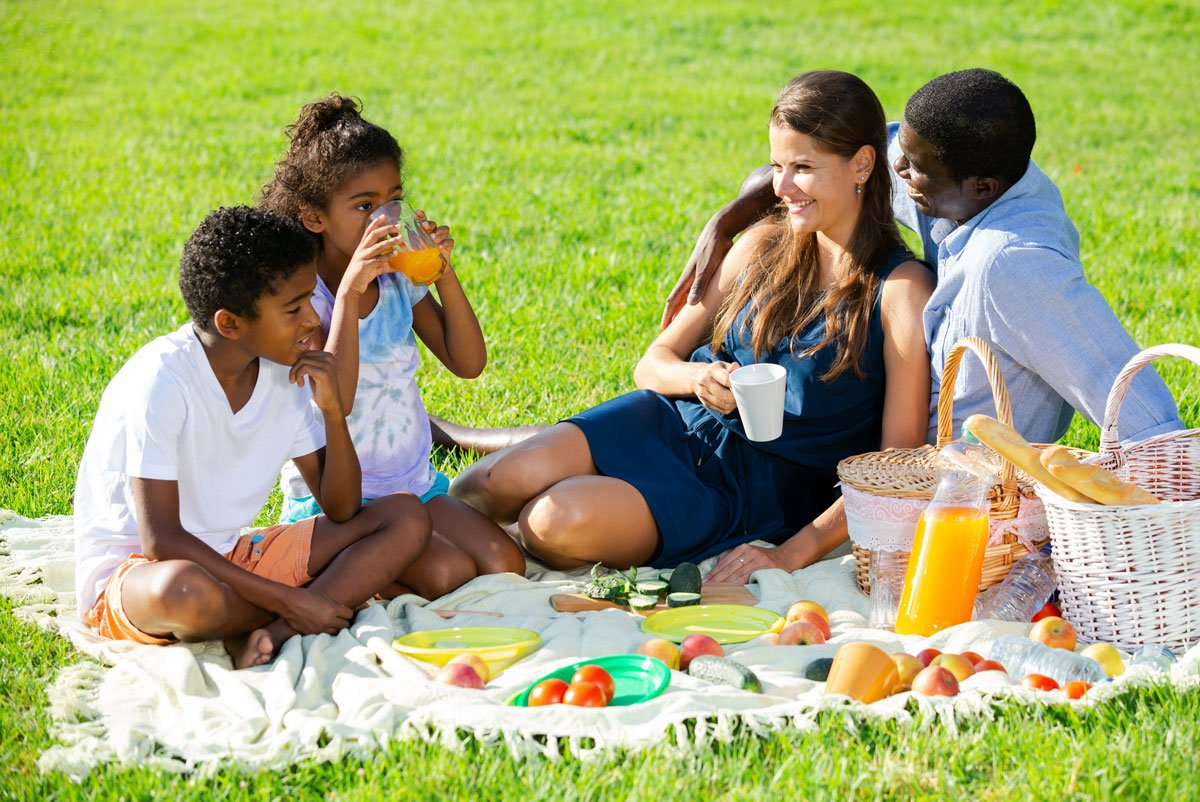 Family enjoying picnic on lawn where bio-herbicides were used